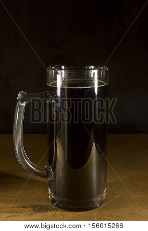Glass with dark kvass on a wooden background
