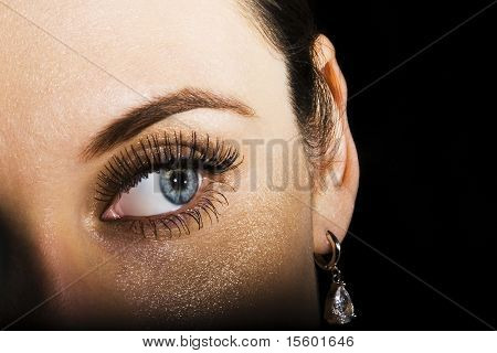 Woman with beautiful earring on black.