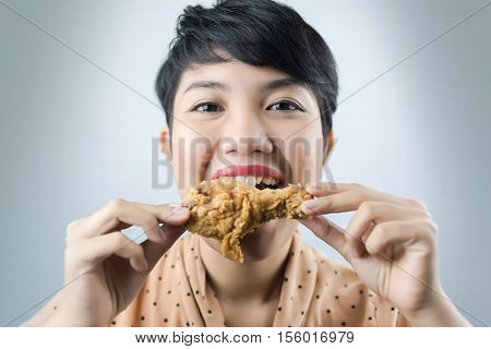 woman to eat deep fried chicken on gray bacground