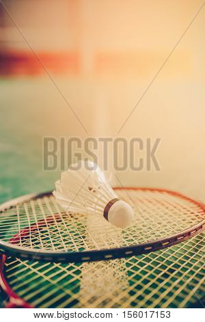 Vintage tone. Badminton ball (shuttlecock) and racket on court floor. Badminton sports. Play badminton. Badminton exer cise. Badminton tournament. Badminton training. Badminton feather. Badminton health. Shuttle badminton.