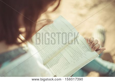 A Young Woman Reading A Book. Book In Woman Hands