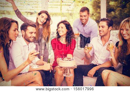 Woman celebrating her birthday with friends against flying colours