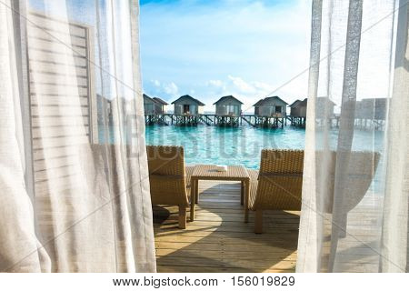 Beautiful tropical Maldives resort hotel with beach and blue water.