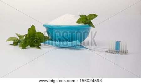 Natural tooth whitening and dental care with a bowl of baking soda, fresh mint and a turquoise blue toothbrush against a white background at eye level with toothbrush bristles facing up.