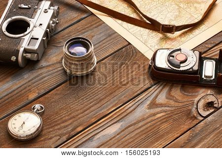 Vintage old 35mm camera, lens and light meter on wooden background with antique XIX century map