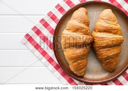 Tasty buttery croissants on plate.