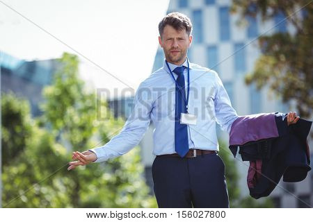 Portrait of handsome businessman standing with blazer near office building