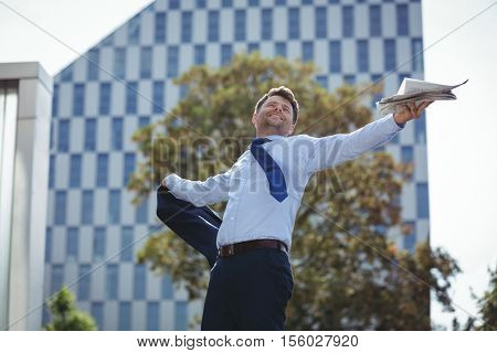 Carefree businessman holding blazer and newspaper near office building