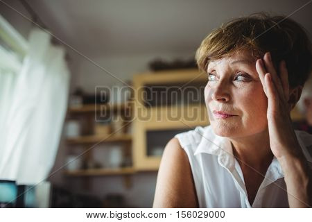 Worried senior woman with hand on forehead at home poster