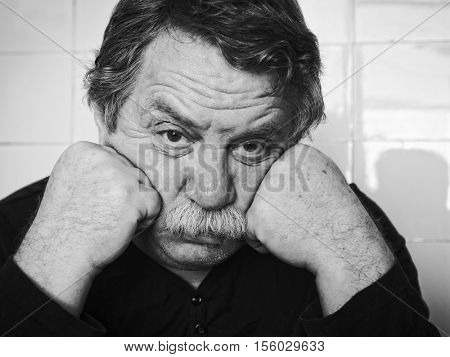 lack and white monochrome photo. Portrait of a sad adult man with a gray mustache.