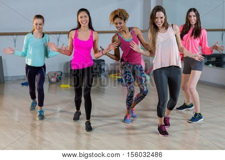 Group of women performing aerobics in gym