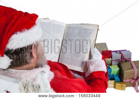 Santa claus reading bible with christmas present beside him against white background