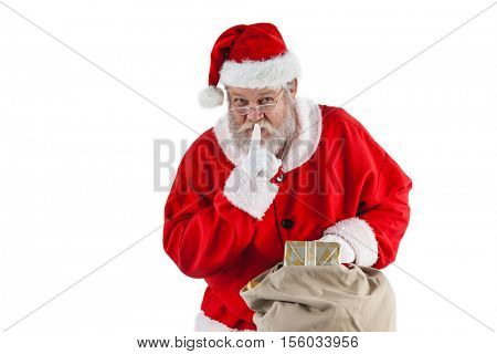 Santa claus with finger on lips and holding a gifts against white background