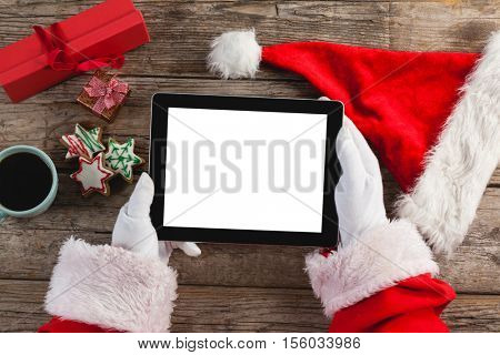 Hand of santa claus using digital tablet on wooden plank