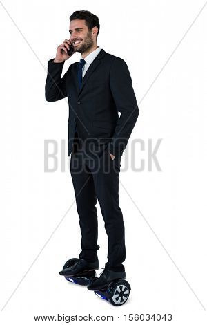 Businessman on hoverboard talking on mobile phone against white background