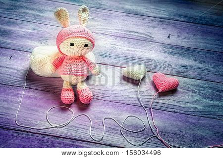 Handmade crochet rabbit toy doll sitting on a skein of wool two crocheted baloons and love inscription made from the thread space for text