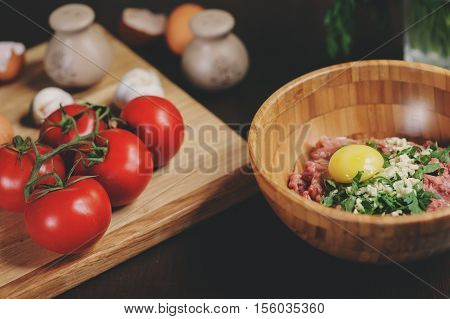 Raw minced meat with egg herbs and fresh tomatoes on wooden table. Ingredients for cooking meat balls or loaf in rustic kitchen