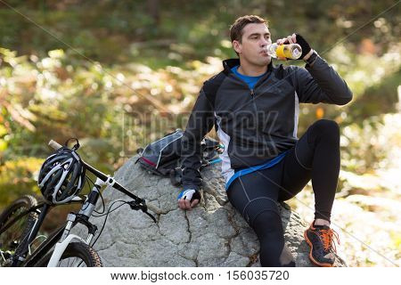 Portrait of male biker drinking water in forest at countryside