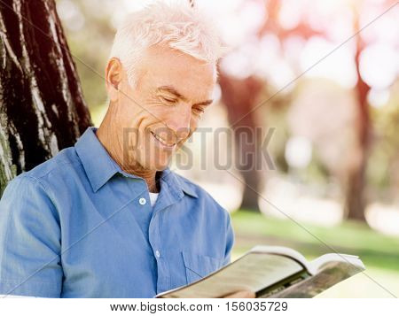 Senior man sittingin park while reading book