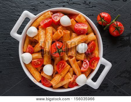 Penne pasta with sauce mozzarella cheese and cherry tomatoes in white round pan on black stone background top view.