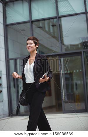Smiling businesswoman holding digital tablet in office premises