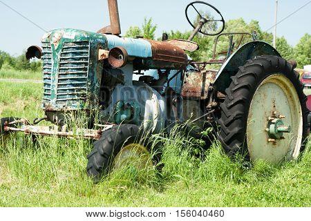 Old rusty blue green definitely broken farm tractor