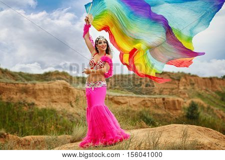 Oriental Beauty belly dancer. Nice girl in national dress dancing with shawl outdoors. Nomads.