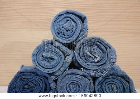Rolled jeans stack on wooden background