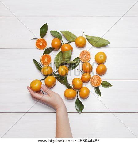 Female hand picks Tangerine (mandarin). White wooden background