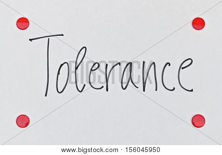 Word Tolerance written on bright background with red pins
