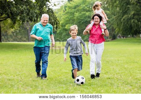 Happy Family Playing Soccer Game Together Running For Ball