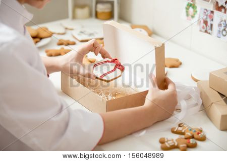 Process of packing gingerbread cookies into a cardboard kraft box, close up, female hands. Christmas concept photo, lifestyle