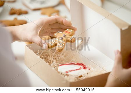 Close up of confectioner hand packing an amazing traditional Christmas gingerman into a cardboard craft box. Christmas concept photo, lifestyle