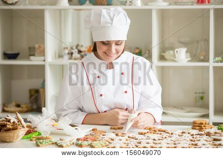 Professional smiling female confectioner decorating gingerbread stars with icing sugar using a pastry bag, makeing lovely homemade tasty Christmas presents. Lifestyle