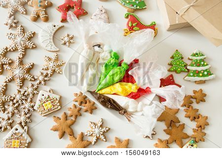 Top view of christmas gingerbread bakes and pastry bags with colorful fillings, glossy sugar cookies. Color sweet Christmas presents concept photo. Small business or Ideas to make fun with kids