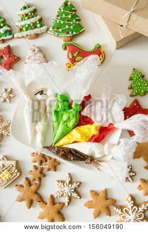 Top view of christmas gingerbread bakes and pastry bags with colorful fillings, perfectly iced sugar cookies. Ideas to make fun with kids. Color sweet Christmas presents concept photo, vertical