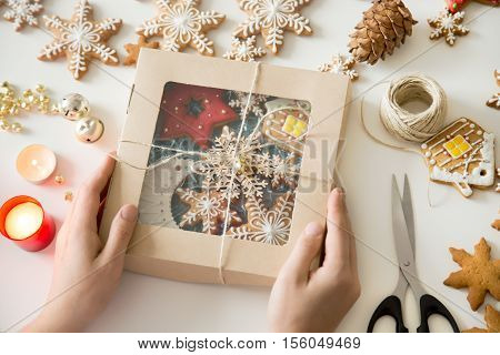 Close up of hands holding a festive box on a white desk, with not boring wrapping, adding gifts some DIY personality, Christmas cookies inside. Christmas concept photo