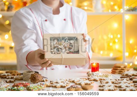 Hands of professional smiling confectioner showing a box with beautifully decorated gingerbread cookies. Christmas mood interior, lightings and candles. Christmas concept photo