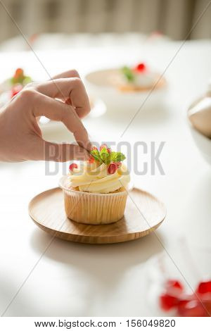 Close up of female hand decorating a cupcake with refreshing mint leaf or picking it. Pastry chef woman making sweet dessert cake