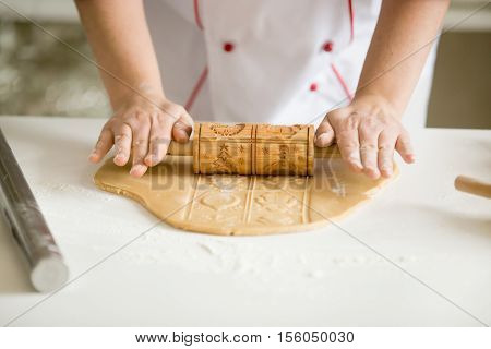 Close up of professional confectioner hands rolling thing gingerbread dough using antique look rolling pin with Christmas pattern. Baker self-employed woman wearing uniform making sweet xmas cookies in her small workshop indoors