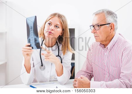 Doctor is showing x-ray snapshot to her patient.