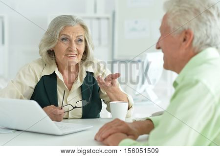Two senior businespeople discussing something looking at each other