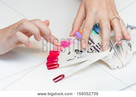 the girl chooses the color of Polish for manicure. testers nail Polish