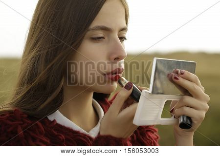 Pretty girl young beautiful woman paints lips with lipstick looking in compact mirror on natural background