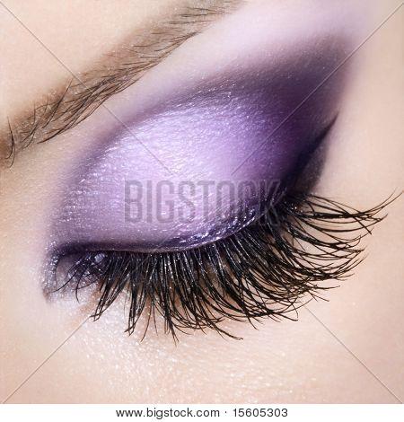 Woman eye with extremely long eyelashes. Purple makeup.