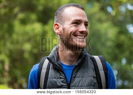 Smiling male hiker hiking in forest