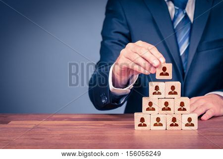 Human resources corporate hierarchy concept and multilevel marketing - recruiter complete team represented by wooden cube by one leader person (CEO) and icon.