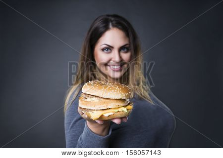 Happy beautiful young plus size model posing with hamburger on a gray studio background xxl woman eating burger fast food and unhealthy nutrition concept