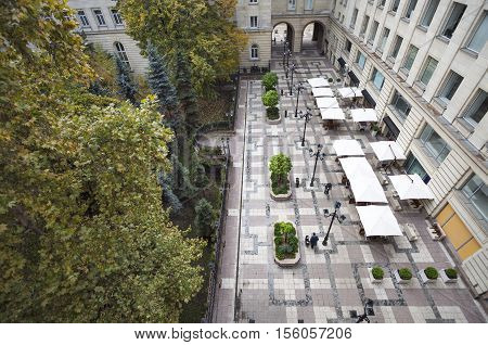 A horizontal view of a walkway with trees and a cafe in downtown Sofia, Bulgaria