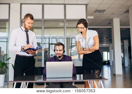 two men and a woman working in the call center